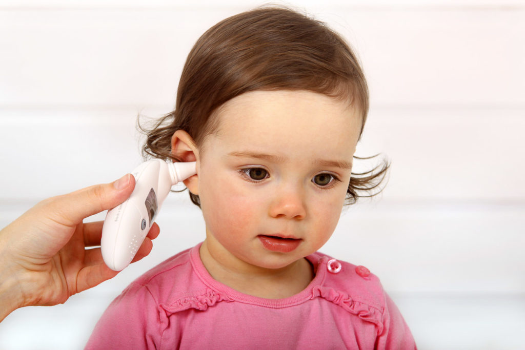 Einem Kleinkind wird im Ohr Fieber gemessen