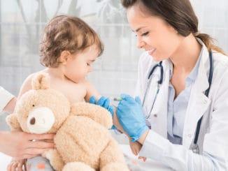 Junge Frau Kinderarztin führt eine Impfung eines kleinen Mädchens durch. Das Mädchen hält ein Maskottchen.